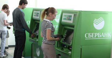 Девушка оплачивает кредит через терминал Сбербанка