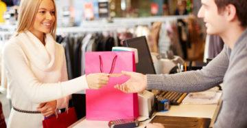 Девушка расплачивается картой Халва в магазине